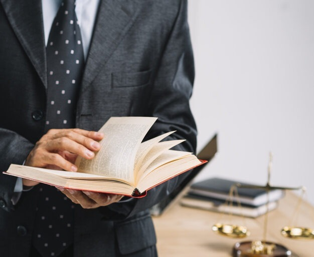 male lawyer reading book standing front desk 23 2147898514 - arbitral award in Dispute Settlement